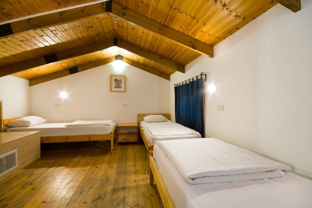 חדר שינה בקומת הגלריה בבקתה משפחתית במתחם חורש