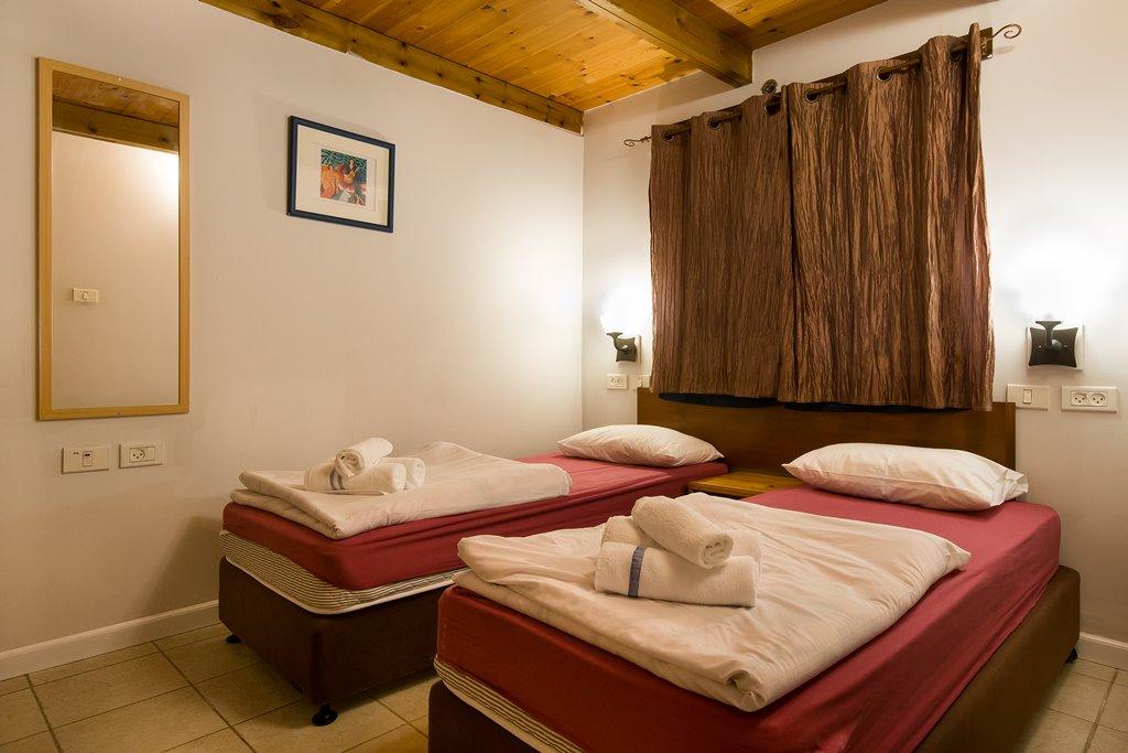 חדר שינה מיטות נפרדות בבקתה במתחם חורש